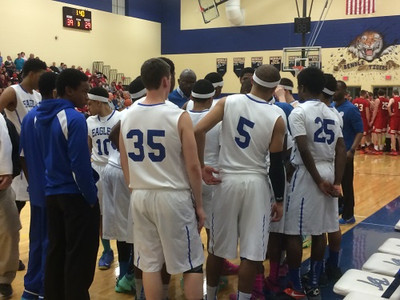 The Southfield Christian basketball team huddles together during a time out (The Oakland Press/Drew Ellis).