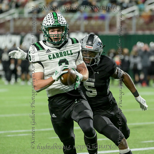 #6 Carroll WR Landon Samson closes in on the goal line while #5 Martin CB Lenard Lemons tries to wrap him up from behind.