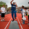 Athlete jumps as volunteer judges look on.