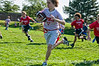 4th grade boys in a touch football game pursue a running back with the football