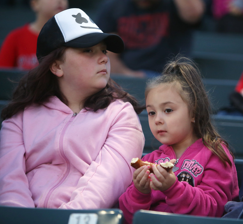 . Lowell Spinners baseball opening day game vs Connecticut Tigers. Angelina Venezia, 4, of Tewksbury, eating a pretzel, with her sister Isabella Venezia, 10.  (SUN/Julia Malakie)