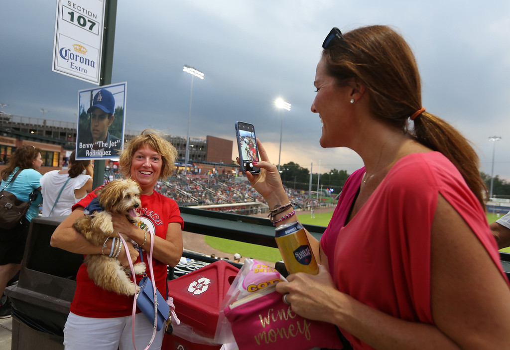 . Fans at Lowell Spinners. Kathy Acciavatti of North Reading, left, holding her Morkie (Maltese/Yorkie), Betty, on Tuesday Dog Night at Spinners, gets Heather Sweeney of Amherst, N.H., to take her picture. (SUN/Julia Malakie)