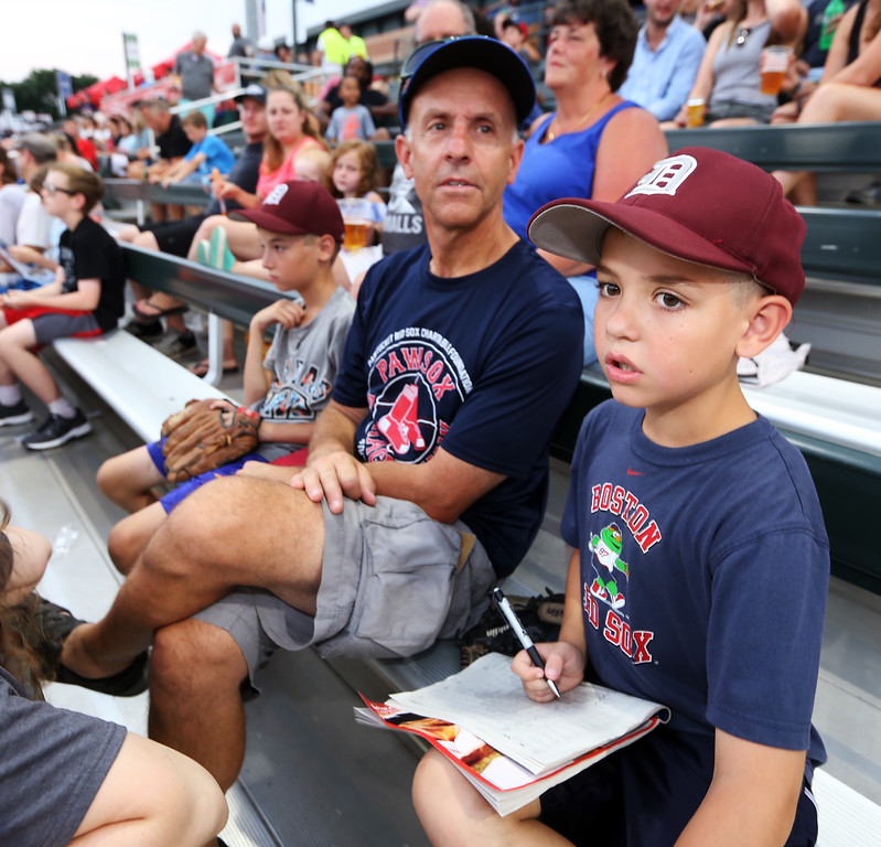 . Fans at Lowell Spinners. John Scaramuzzo of Dedham with his son James, 8, who was filling out a baseball scoresheet for the first time. (SUN/Julia Malakie)