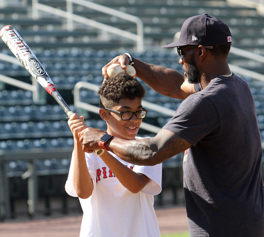 . Lowell Spinners and Eastern Bank hold kids\' baseball camp. Spinners manager Corey Wimberly helps Irwin Edwards, 11, of Lowell, with his batting stance.(SUN/Julia Malakie)