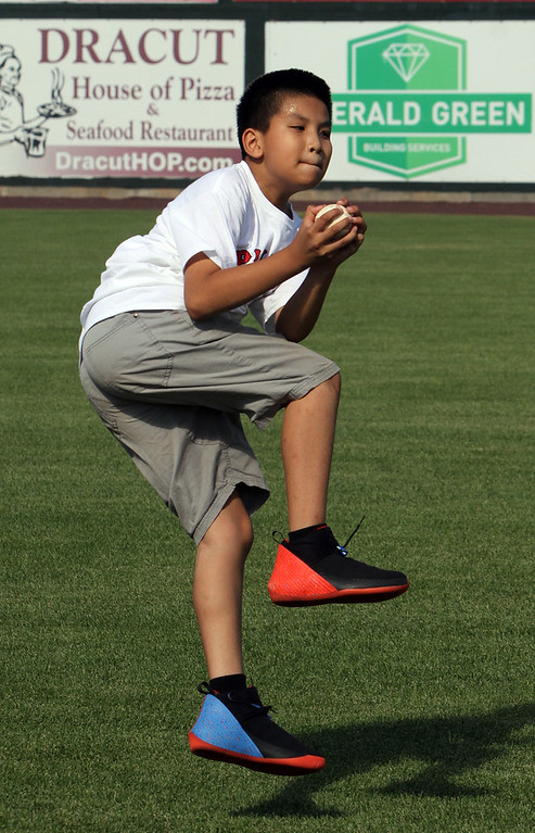 . Lowell Spinners and Eastern Bank hold kids\' baseball camp. Kevin Tuon, 11, of Lowell, catches a ball during drill catching fly balls, for several players who didn\'t have gloves with them. (SUN/Julia Malakie)