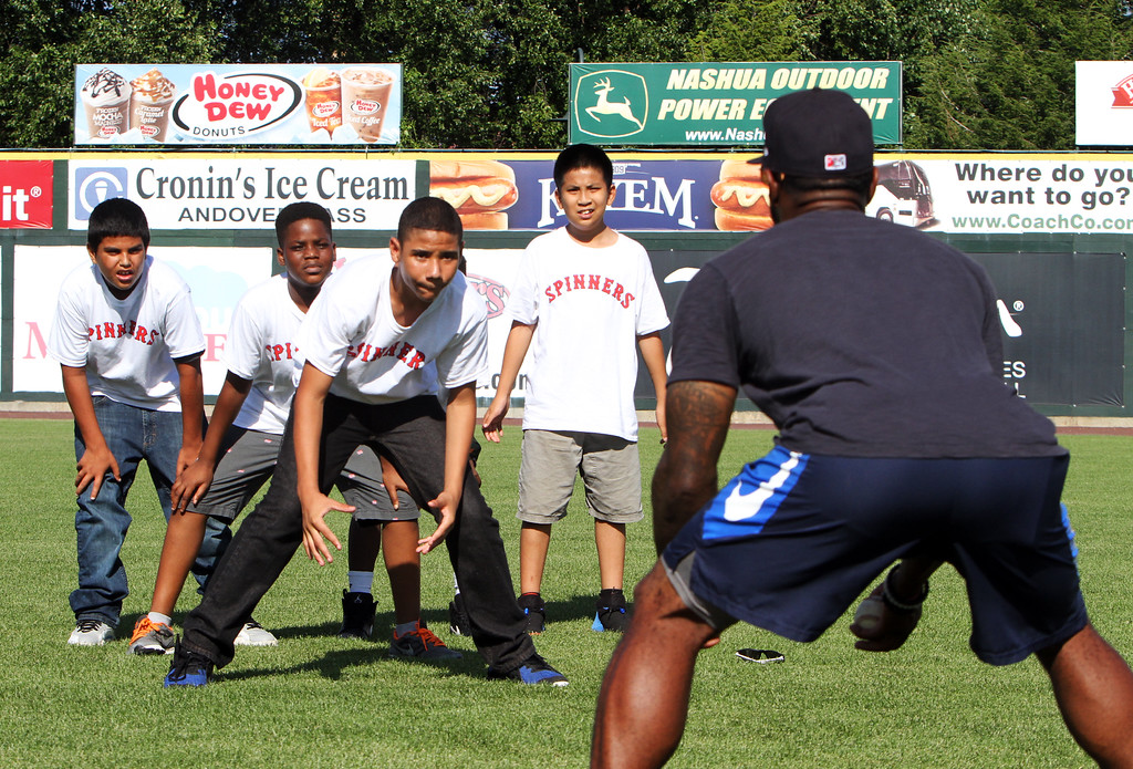 . Lowell Spinners and Eastern Bank hold kids\' baseball camp. From left, Jonatan  Torres, 10, Nana Donkor, 11, Jaquawn Williams, 13, Kevin Tuon, 11, all of Lowell, and Spinners manager Corey Wimberly, coaching them on fielding position. (SUN/Julia Malakie)