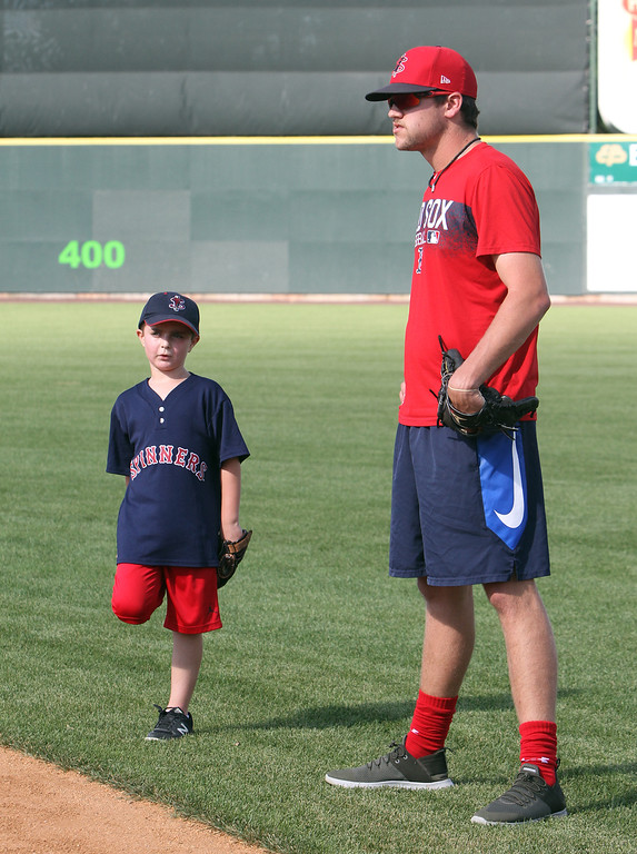 . Lowell Spinners and Eastern Bank hold kids\' baseball camp. Owen Bushway, 8, of Lewiston, Maine, talks with Spinners\' Hunter Haworth while waiting to field ground balls. (SUN/Julia Malakie)