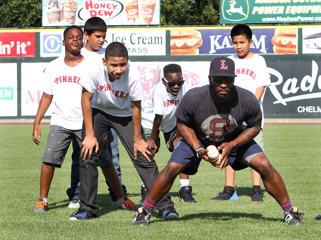 . Lowell Spinners and Eastern Bank hold kids\' baseball camp. Spinners manager Corey Wimberly works on fielding with, from left, Nana Donkor, 11, Jonatan  Torres, 10, Jaquawn Williams, 13, Dominic Kasune, 11, and Kevin Tuon, 11, all of Lowell. (SUN/Julia Malakie)