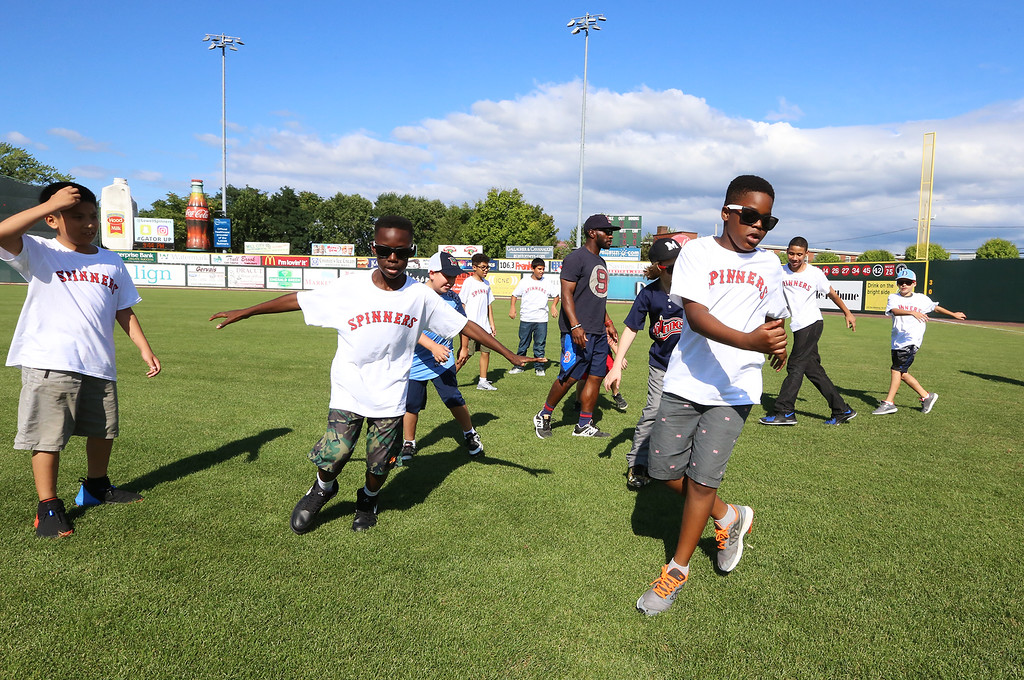 . Lowell Spinners and Eastern Bank hold kids\' baseball camp. From left, Kevin Tuon, Dominic Kasune, and Nana Donkor, all of Lowell, run sideways during warmup exercises.  (SUN/Julia Malakie)