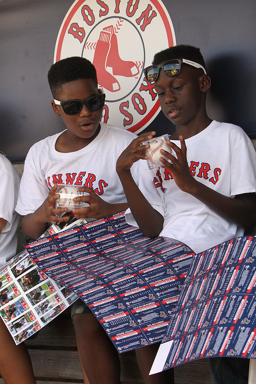 . Lowell Spinners and Eastern Bank hold kids\' baseball camp. Dominic Kasune, 11, left, and Nana Donkor, 11, both of Lowell, look at their David Ortiz-autographed baseballs. (SUN/Julia Malakie)
