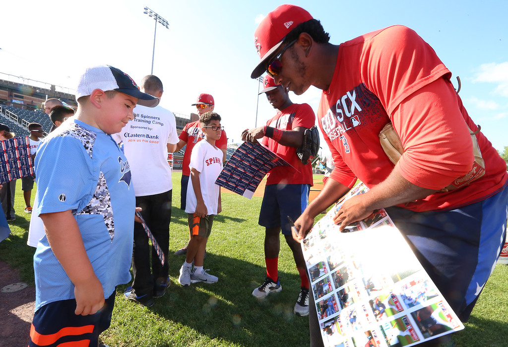 . Lowell Spinners and Eastern Bank hold kids\' baseball camp. Spinners pitcher Victor Garcia signs his autograph for Jacob Madruga, 9, of Dracut. (SUN/Julia Malakie)