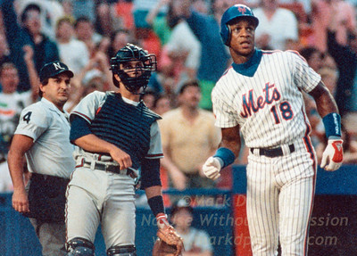 New York Mets Daryl Strawberry watches homerun on July 21, 1990 against the Atlanta Braves as catcher Jimmy Kremers and umpire Mark Hirschbeck lean with it.