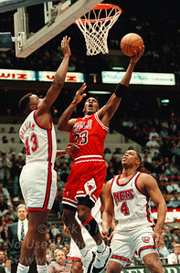 Chicago Bulls Michael Jordan goes up for a layup against Jaysen Williams of the New Jersey Nets as Nets Rick Mahorn watches.