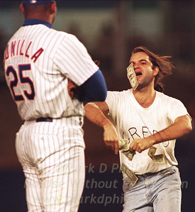 Fan wearing a Greed Tshirt throws dollar bills at New York Mets player Bobby Bonilla.