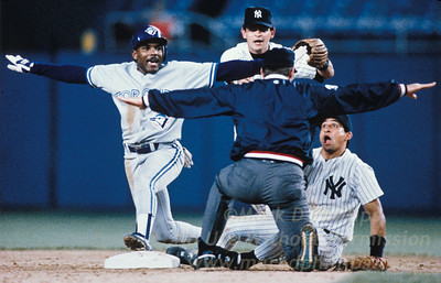 Toronto Blue Jays Manny Lee signal safe, mirroring the umpire, after breaking up a double play to the shock of NY Yankees Andy Stankowitz (looking up in amazement) and Mike Gallego charging in from behind. 1992 Baseball Hall of Fame First Place Action and First Place Sports Action in 1992 Pictures of the Year. ©Mark D Phillips