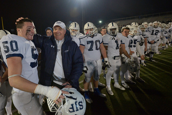 Waltham: St. John's Prep coach Jim O'Leary celebrates with captain James Fagan while the Eagles line up to receive the Super Bowl trophy. Mark Teiwes photo.