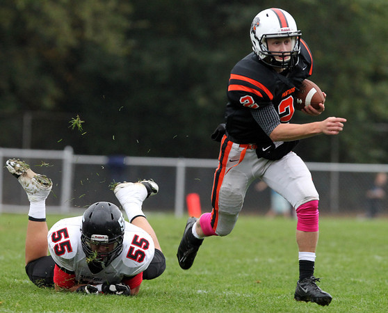 Beverly: Beverly senior quarterback Nick Manthorne (2) manages to elude the tackle from Marblehead senior Tom Koopman (55) and breaks towards the sideline on Saturday afternoon. David Le/Salem News