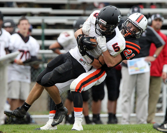 Beverly: Marblehead senior wide receiver Dylan Cressy (5) hangs onto the ball tightly as Beverly senior Nick Donovan (21) drags him down. David Le/Salem News