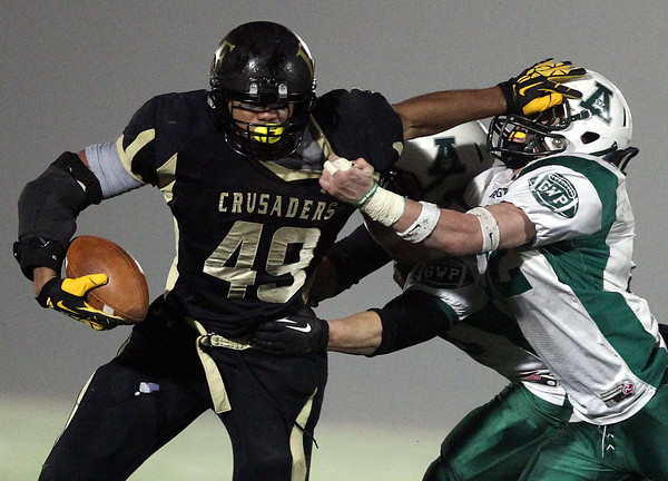 Woburn: Bishop Fenwick junior running back Rufus Rushins (49) stiff arms Abington senior linebacker Scott Jansen (52) as he powers his way for a Crusaders first down during the first half of the D5 State Semifinal at Connolly Stadium in Woburn on Friday evening. David Le/Salem News