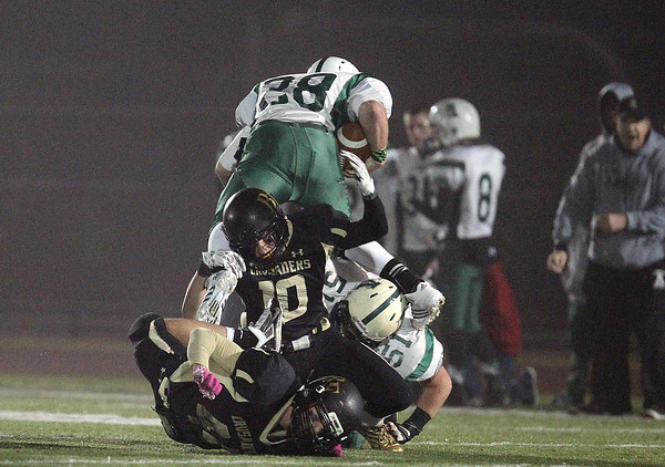 Woburn: Bishop Fenwick senior Tom Parson (10) flips Abington senior Matt Kilmain (28) over his head as he brings down the Green Wave ballcarrier down during the D5 State Semifinal at Connolly Stadium in Woburn on Friday evening. David Le/Salem News