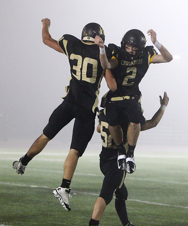 Woburn: Bishop Fenwick junior Brian Fitzpatrick (30) and senior Kevin Hannon (2) leap in the air and celebrate the Crusaders 35-8 win in the D5 State Semifinal at Connolly Stadium in Woburn on Friday evening. David Le/Salem News