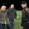 Peabody: Bishop Fenwick football head coach Dave Woods, right, greets former Crusaders running back Bobby Tarr and his mother Mary Beth Haggerty during a halftime presentation where Tarr's number 3 was retired by Bishop Fenwick. David Le/Salem News