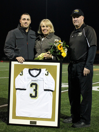Peabody: Bishop Fenwick football head coach Dave Woods, right, with former Crusaders running back Bobby Tarr and his mother Mary Beth Haggerty during a halftime presentation where Tarr's number 3 was retired by Bishop Fenwick. David Le/Salem News