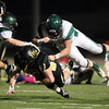Peabody: Bishop Fenwick's David Hurley (56) plows ahead while being brought down by Austin Prep's Damian Dell'anno (43) and Nick Mulcahy (30) on Friday evening. David Le/Salem News