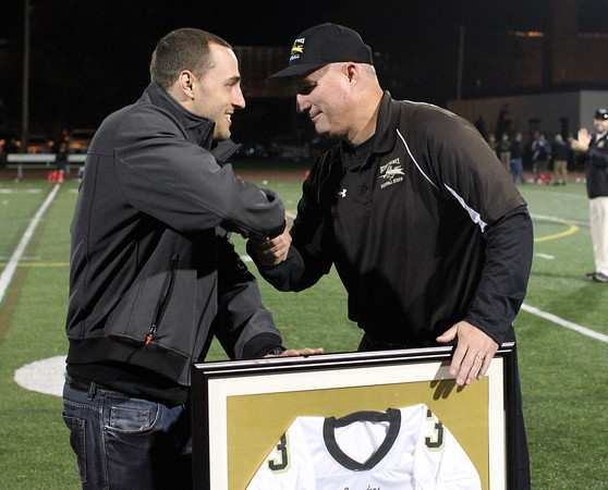 Peabody: Bishop Fenwick football head coach Dave Woods, shakes hands with former Crusaders running back Bobby Tarr during a halftime presentation where Tarr's number 3 was retired by Bishop Fenwick. David Le/Salem News