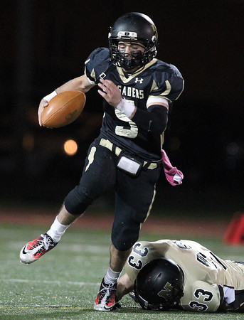 Peabody: Bishop Fenwick senior captain Nick Bona (5) shakes loose from a tackle from Northeast senior Craig Carucci (33) and sprints upfield for a big gain on Friday evening. David Le/Salem News