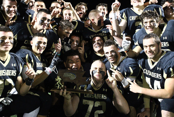 Peabody: The Bishop Fenwick football team holds up the D5 North Championship trophy after handily beating Northeast Regional on Friday evening. David Le/Salem News