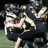 Peabody: Bishop Fenwick senior Kevin Hannon (2) drags down Northeast running back Christian Perez (23) during the first half of play on Friday evening in the D5 North Final. David Le/Salem News