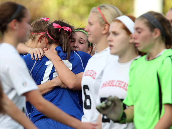 Marblehead: Danvers junior Emily Murphy, left, senior Courtney Arnoldy, center, and senior Cate Raftery, right, hug each other after the Falcons defeated Marblehead on PK's to advance in the D2 North first round game on Friday afternoon at Piper Field in Marblehead. David Le/Salem News
