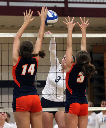 Wenham: Gordon sophomore Jessica Burdick (3) spikes the ball over the net past the outstretched arms of Salem State sophomore Emily Peay (14) and senior captain Mackenzie Carpenter (3) on Saturday morning. David Le/Salem News