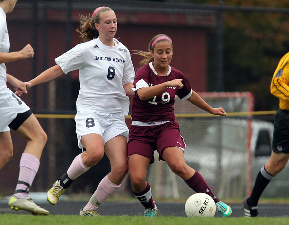 Hamilton: Newburyport senior captain Jaycie Triandafilou (19) crosses the ball into the box while being pressured by Hamilton-Wenham senior captain Carolyn Cook (8) on Wednesday afternoon. David Le/Newburyport Daily News