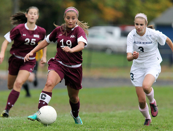 Hamilton: Newburyport senior captain Jaycie Triandafilou (19) carries the ball upfield while being pursued by Hamilton-Wenham sophomore Emma Beane (3) on Wednesday afternoon. David Le/Newburyport Daily News