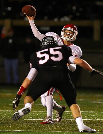Marblehead: Masco senior quarterback Troy Bunker (14) unleashes a deep throw as Marblehead senior Tom Koopman (55) bears down on him. David Le/Salem News