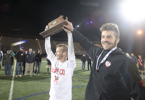 Lynn: Masco senior captains Adam Grammar (11) and Jeff Panella (27) hoist the D2 State Championship trophy above their heads after the Chieftans defeated Walpole 4-2 on Thursday evening. David Le/Salem News