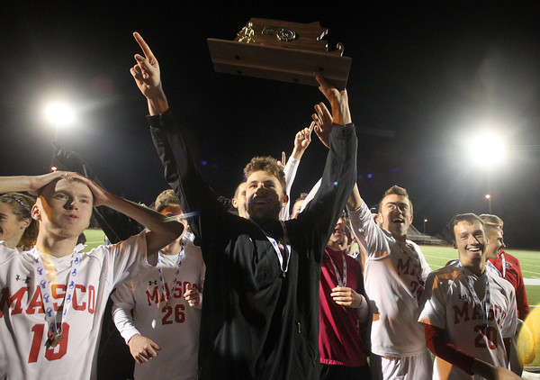 Lynn: Masco senior captain Jeff Panella, center, holds the D2 State Final trophy high above his head as the Chieftans boys soccer team goes over to celebrate their win with the crowd. David Le/Salem News