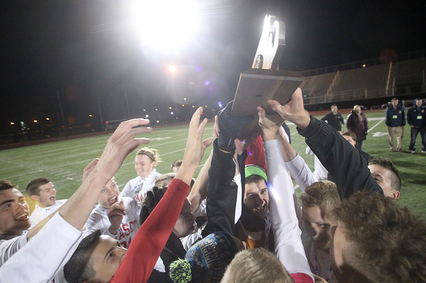Lynn: The Masco boys soccer team hoists the D2 State Championship trophy high above their heads after defeating Walpole 4-2 to capture the state title. David Le/Salem News