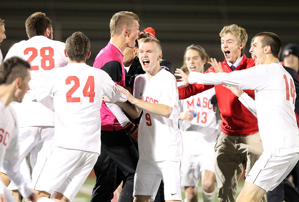 Lynn:  The Masco boys soccer team mobs senior goalie Willie Stewart, center, after the Chieftans defeated Walpole 4-2 on Thursday evening. David Le/Salem News