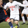 Lynn: Masco senior captain Adam Grammar (11) plays the ball upfield while being pursued by Walpole senior Robert Ivatts (10) during the first half of the D2 State Championship on Thursday evening at Manning Field in Lynn. David Le/Salem News