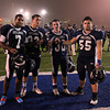 Braintree: North Shore Tech captains Yordany Sanchez (7), Daniel Bailey (33), Ian LaFavour (30), and John Sabbio (55) hold up the runners up trophy for the Massachusetts Vocational Small School Division Championship on Thursday evening after falling to Blue Hills 23-22. DAVID LE/Staff Photo