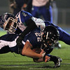 Braintree: North Shore Tech senior running back Ross Murphy (33) dives forward for a few more yards while being brought down by Blue Hills junior Orane Gordon (24) during the first half of play on Thursday evening. DAVID LE/Staff Photo