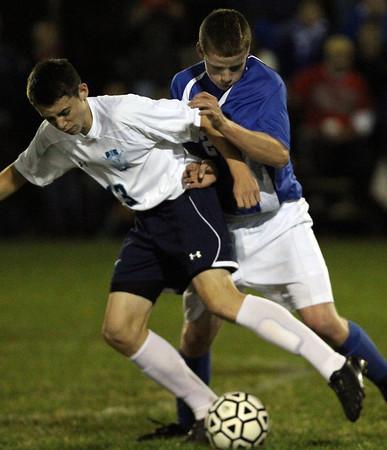 Peabody: Peabody midfielder Kenny Sawyer (13) tries to shield the ball from Danvers forward Mark McCarthy (23) on Wednesday evening. David Le/Salem News