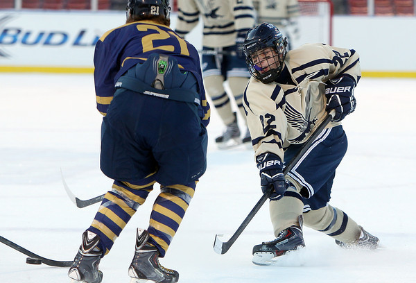 Boston: St. John's Prep sophomore forward Seth Murray (22) rifles a shot on net past Malden Catholic junior Chris Hopkins (21) during the Eagles' Frozen Fenway game against Catholic Conference rival Malden Catholic on Tuesday afternoon. DAVID LE/Staff Photo