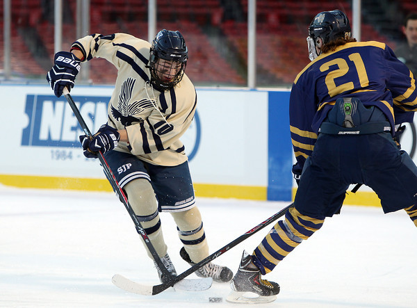 Boston: St. John's Prep junior forward Nick Latham (10) dekes around Malden Catholic junior defenseman Chris Hopkins during the Eagles' Frozen Fenway game against Catholic Conference rival Malden Catholic on Tuesday afternoon. DAVID LE/Staff Photo