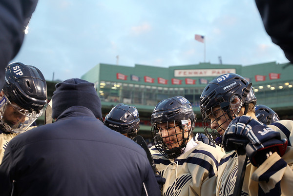 Boston: St. John's Prep players listen intently to head coach Kristian Hansen during a third period timeout during the Eagles' Frozen Fenway game against Catholic Conference rival Malden Catholic on Tuesday afternoon. DAVID LE/Staff Photo