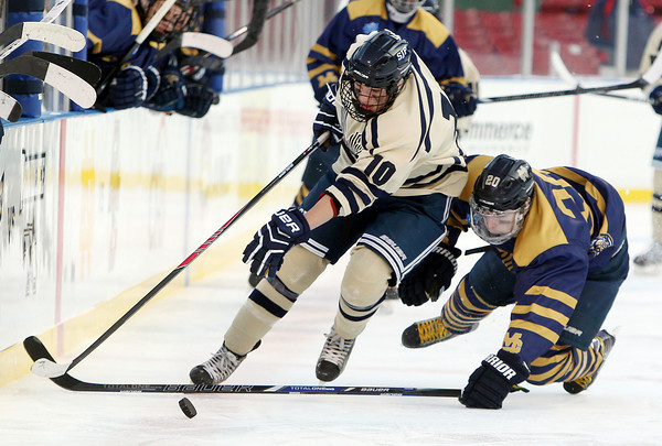 Boston: St. John's Prep junior forward Nick Latham (10) manages to keep his skates and tries to corral the puck as Malden Catholic junior John McLean (20) dives to try and bat the puck away during the Eagles' Frozen Fenway game against Catholic Conference rival Malden Catholic on Tuesday afternoon. DAVID LE/Staff Photo