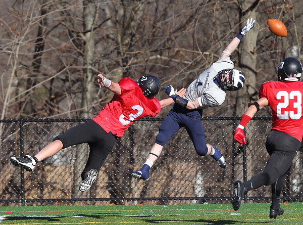 Marblehead: Swampscott senior captain Ben Faulkner (4) leaps high in the air but can't reel in a pass from quarterback Brendan McDonald while being defended by Marblehead junior Spencer Craig (3), during the second half of the Magicians 51-13 thumping of the Big Blue on Thanksgiving morning at Piper Field in Marblehead. David Le/Salem News